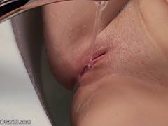 Teen masturbates with the water jet