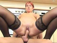 Red-haired granny rides a dick in the kitchen