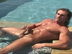 Muscular guy wanks at the pool